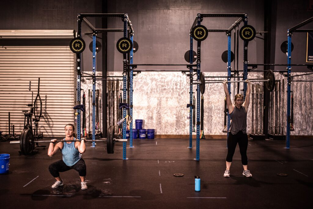 Women performing compound movements with barbells instead of trying to spot reduce fat